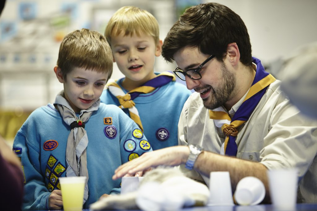 Volunteer Beaver leader showing beaver scout an activity